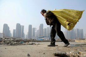 File photo of a rubbish collector carrying a bag on her back as she walks past a construction site near a recently finished residential complex in Hefei