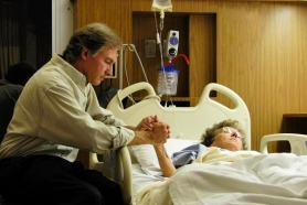 man-sitting-with-older-woman-in-hospital-bed-holding-her-hand
